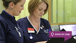Two members of staff discuss patient notes in Frimley Park's emergency department