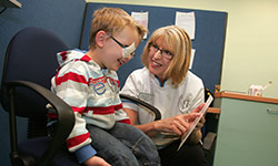 photo of a female clinician with a small boy who is wearing a patch over one eye