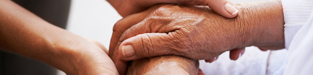 Photo of a carer holding an older woman's hand
