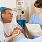 Image of a patient in a hospital bed talking to a nurse