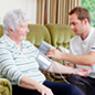 Image of a man being helped by a carer in his home